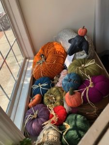 Knit pumpkins piled in the window